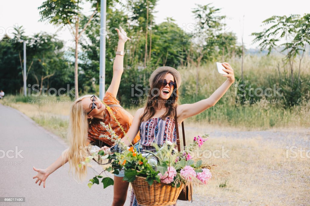 Girl friends are taking selfie on a bike royalty-free stock photo