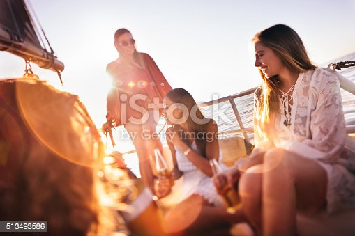 Group of girl friends happy and relaxing on a golden summer evening, enjoying a sunset cruise on a yacht while drinking beer with brilliant sunflare