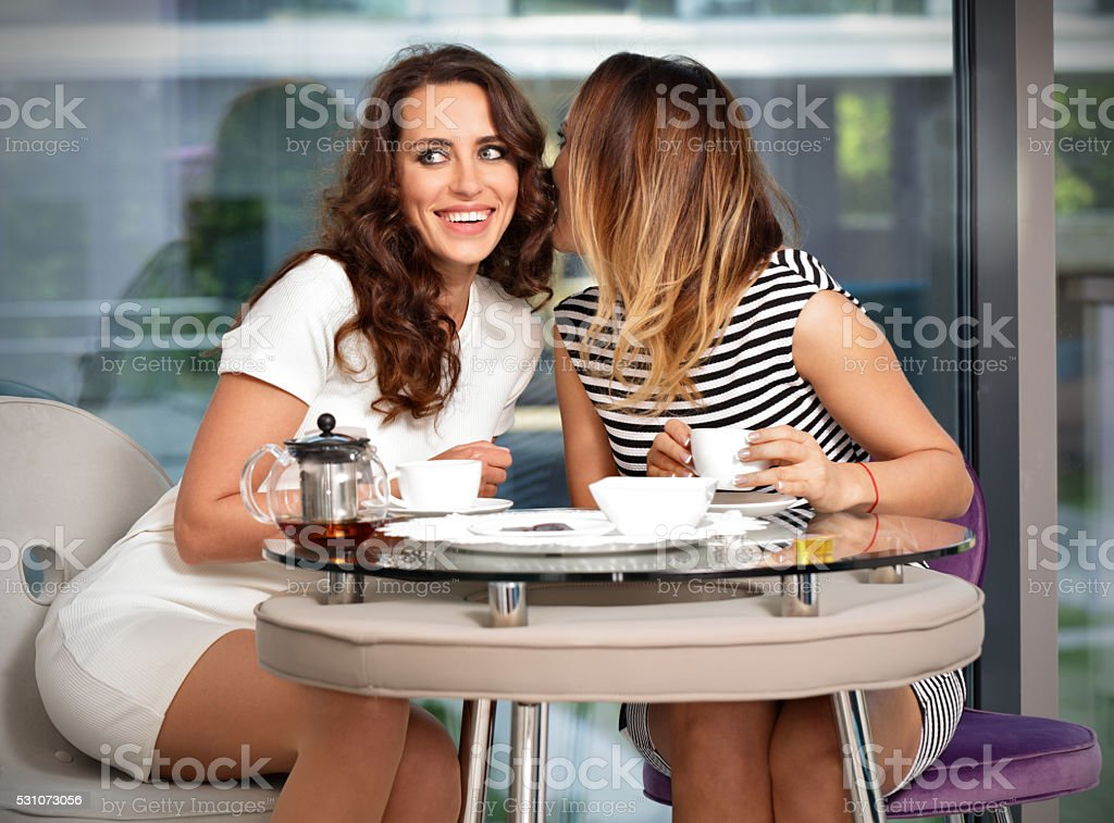 Girl friends in the a cafe gossip stock photo