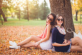 Two female friends sitting and posing under a tree in a park