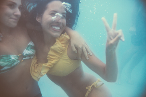 Two teen girl friends underwater showing a peace sign while smiling and posing together in bikinis