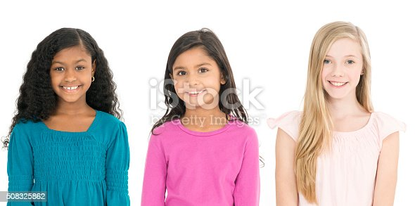A multi-ethnic group elementary age girls are standing together are are smiling while looking at the camera.