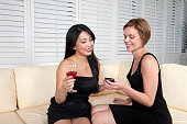 istock Girl Friends With Wine and Smart Phone Holding Hands 889182632