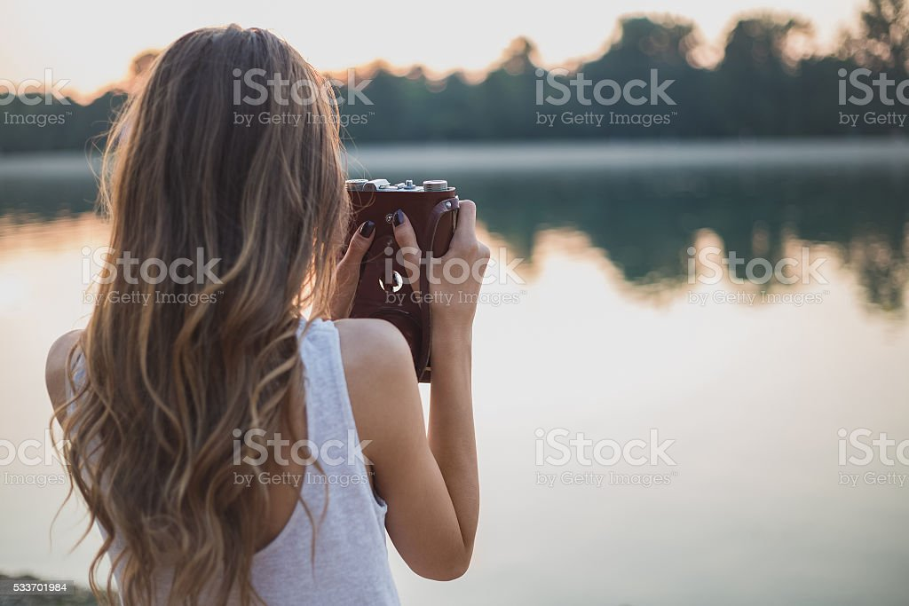 Girl from behind photographing on the beach stock photo