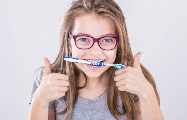 Girl from the dental braces with teethbrush making thumb up hand sign gesture. Orthodontist and dentist concept. stock photo