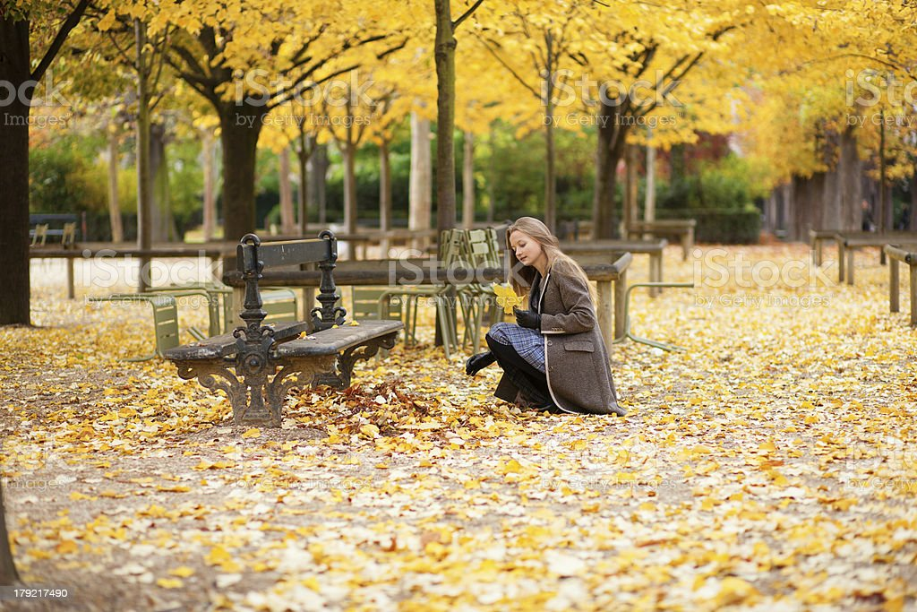 Girl gathering autumn leaves in a park royalty-free stock photo