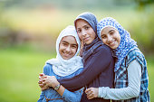 Three Muslim girls of different ages are outdoors in a park. They are embracing and smiling for the camera.