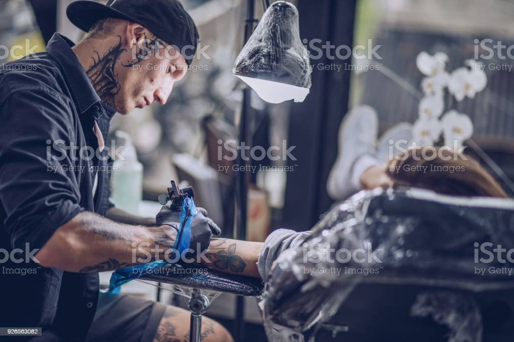 Girl getting arm tattoo stock photo