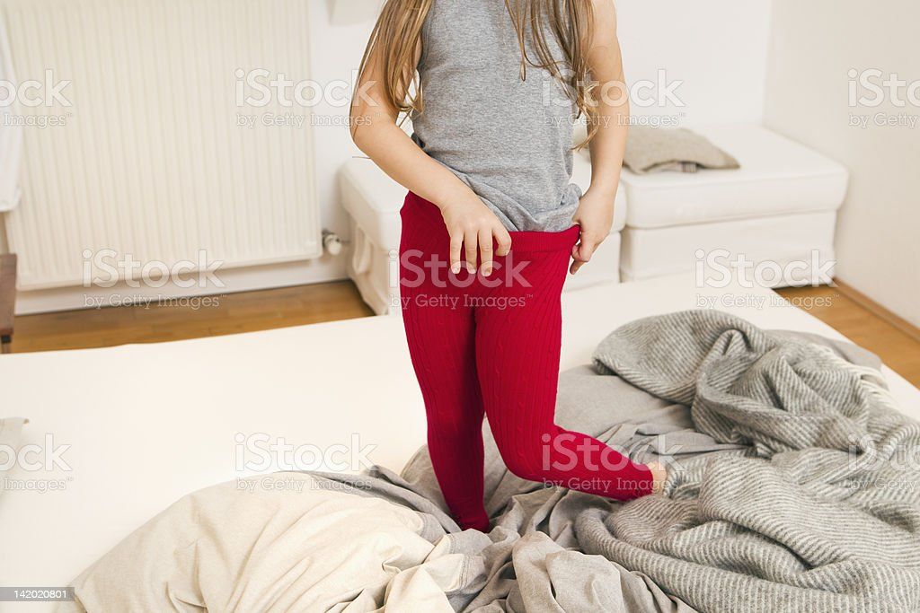 Girl getting dressed on bed stock photo