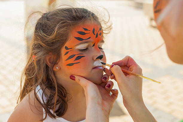 Girl getting her face painted by painting artist. - foto de stock