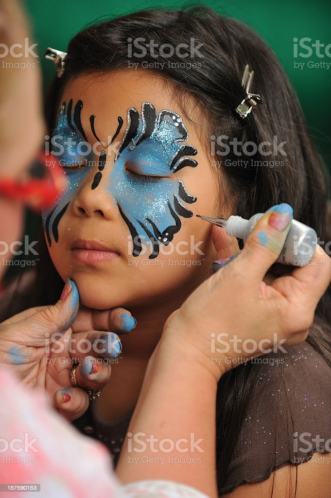 Girl getting her face painted stock photo