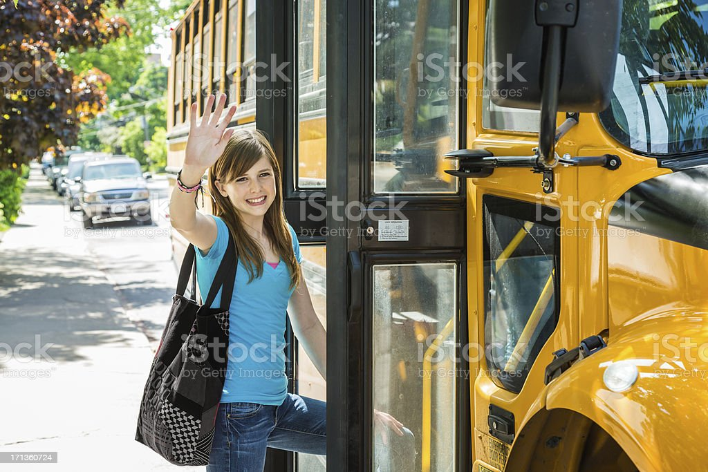 Girl getting on school bus stock photo