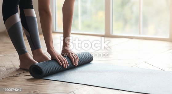 Cropped photo of girl getting ready before morning yoga practice, placing her yoga mat on floor at fitness studio, panorama with copy space