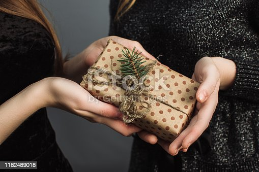 A girl gives a friend a Christmas gift made with her own hands. The concept of Christmas and the new year. Girls in shiny black dresses exchange gifts.