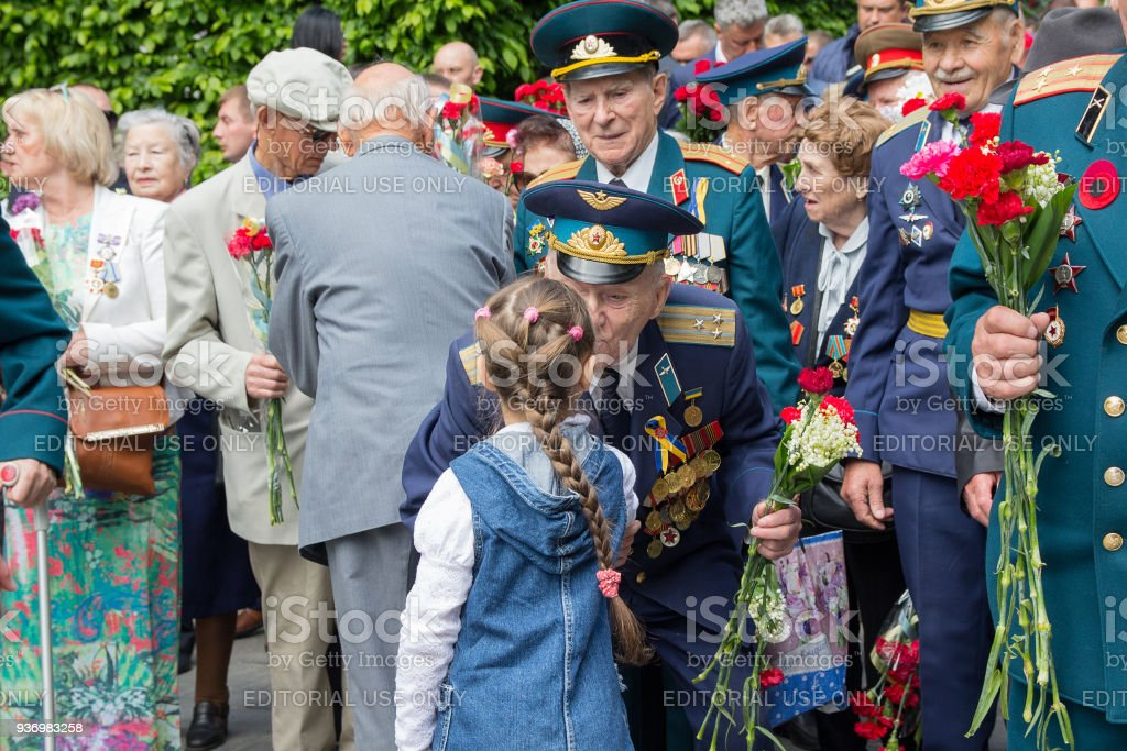 Girl Gives Flowers To The Veterans Of The Great Patriotic