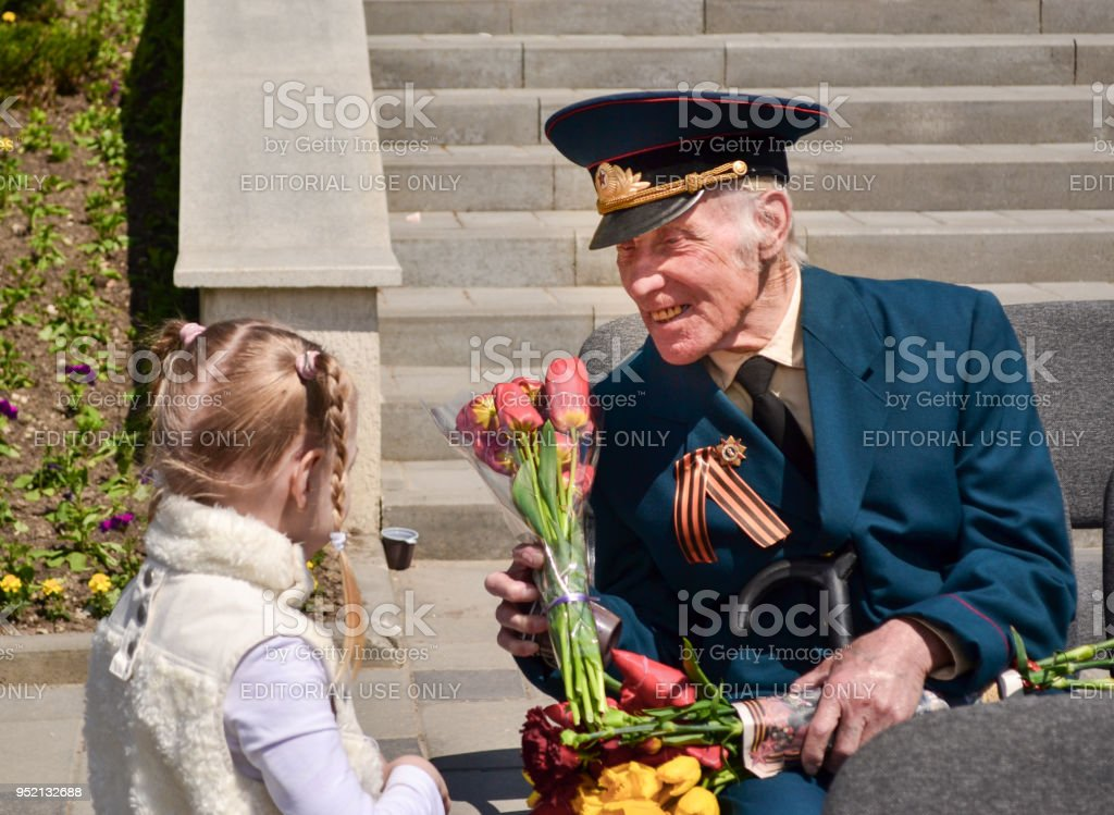 Girl gives flowers to veteran on Victory Day. stock photo
