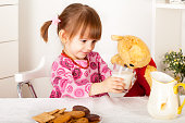 Cute little girl gives a glass of milk to teddy bear