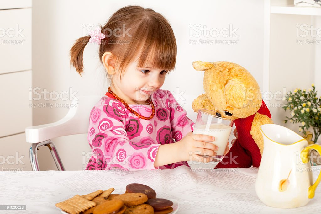Girl gives glass of milk to teddy bear stock photo