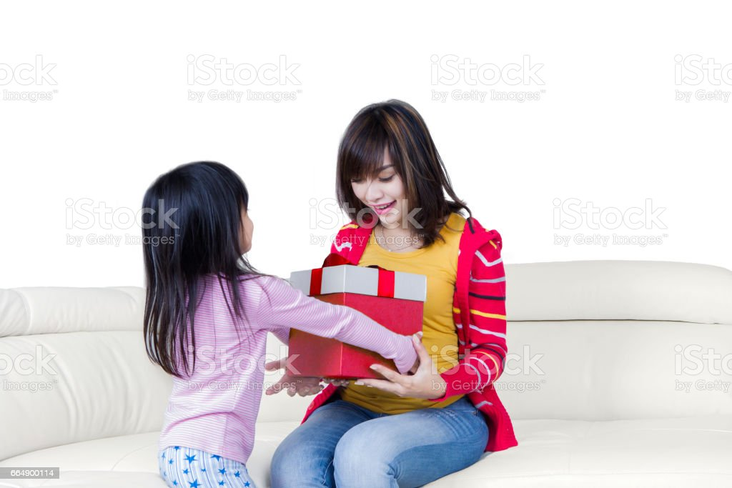 Girl gives presents at her mother on sofa foto stock royalty-free
