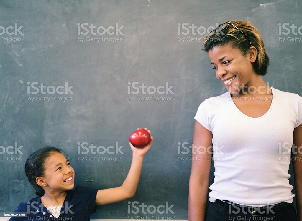 Girl giving an apple to teacher 免版稅 stock photo