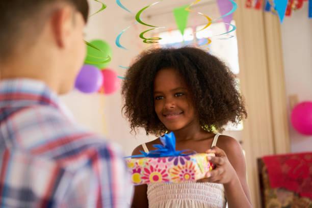 girl giving birthday present to boy classmate - jugendliche geburtstag geschenke stock-fotos und bilder