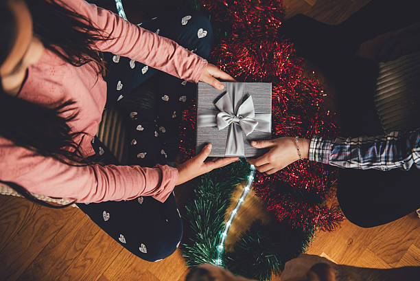girl giving friend christmas gift - christmas gift family bildbanksfoton och bilder