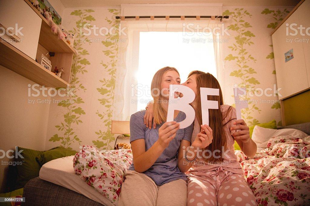 Girl giving her Best Friend Forever a kiss on cheek stok fotoğrafı