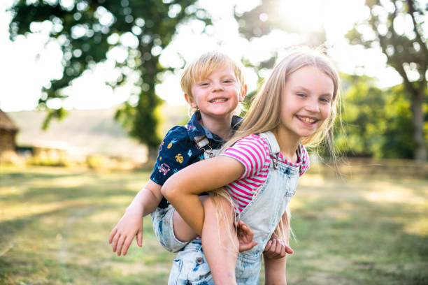 Girl giving her brother a piggyback ride Girl giving her brother a piggyback ride sister stock pictures, royalty-free photos & images