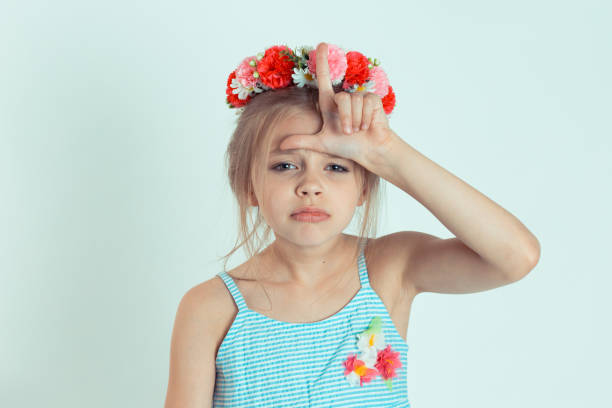 girl giving loser sign on forehead looking at you disgust on face Closeup portrait young unhappy kid girl giving loser sign on forehead looking at you disgust on face isolated on white light green wall background. Negative human emotion face expression body language antagonize stock pictures, royalty-free photos & images