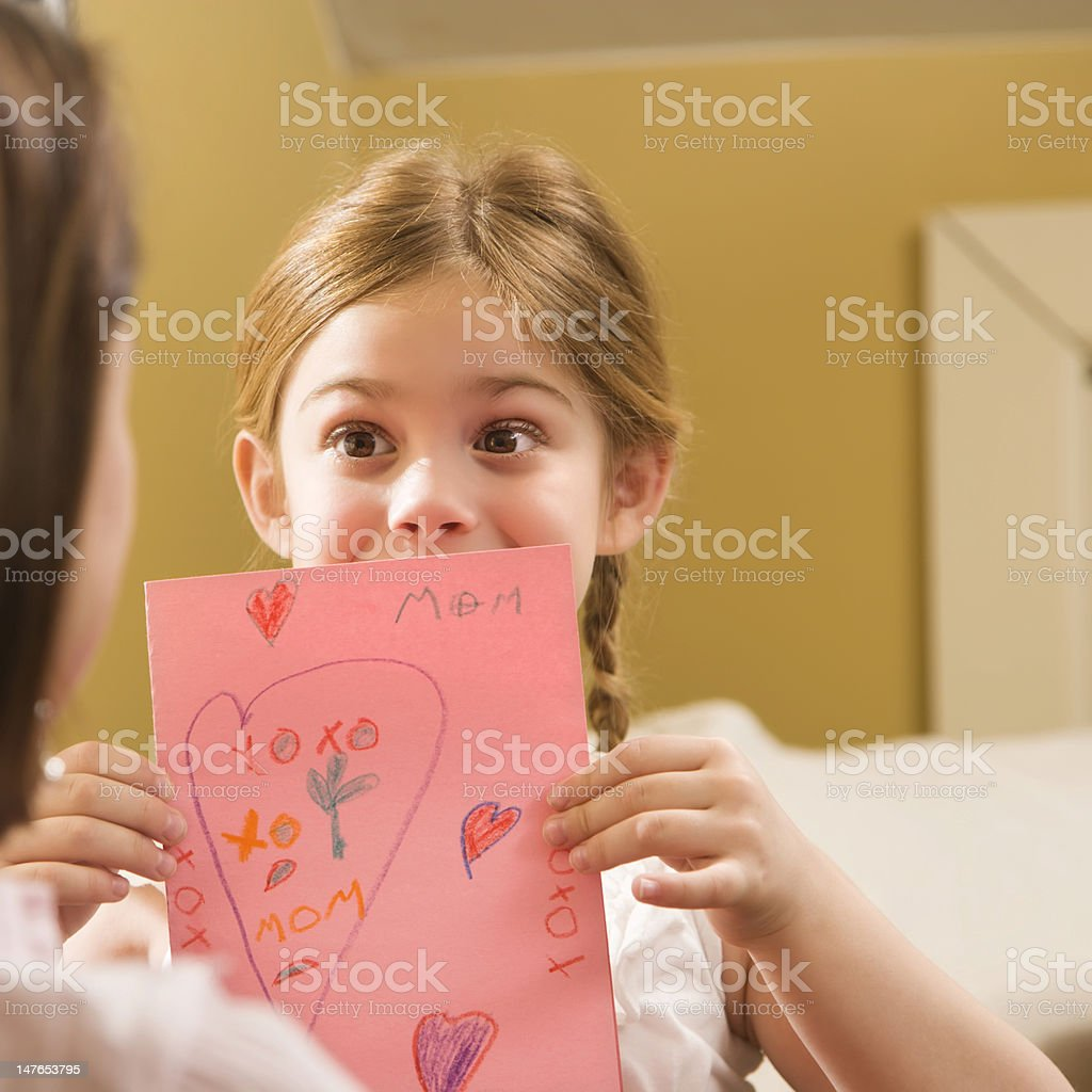 Girl giving Mom a drawing. royalty-free stock photo