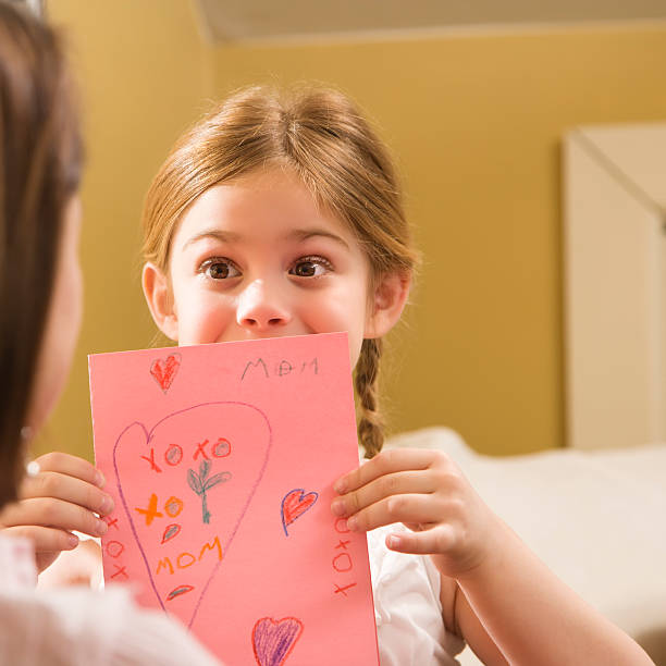 Girl giving Mom a drawing. stock photo
