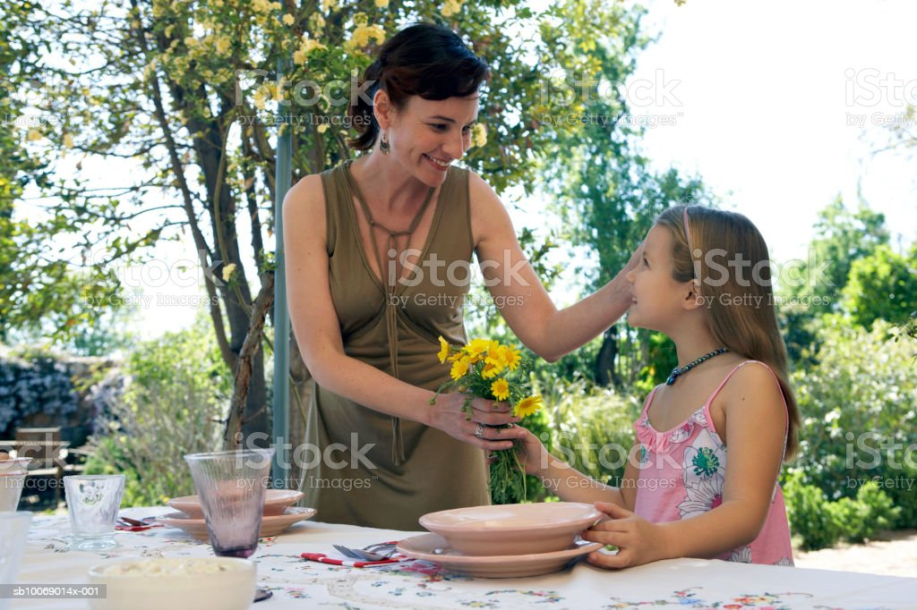 Girl (8-9) giving mother bunch of flowers at dining table royalty-free stock photo
