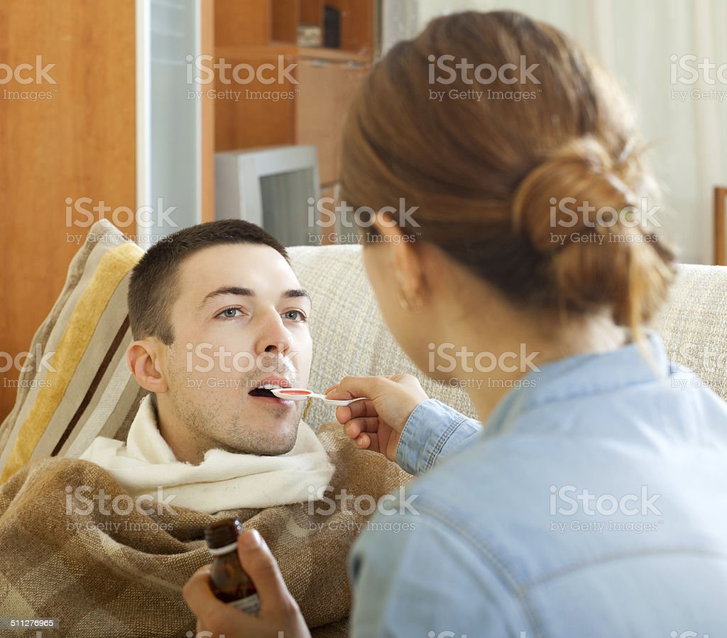 Girl giving syrup to diseased man stock photo