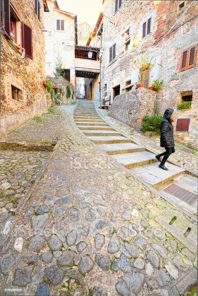 Girl goes down the staircase in the medieval heart of Anghiari, Arezzo, Tuscany stock photo