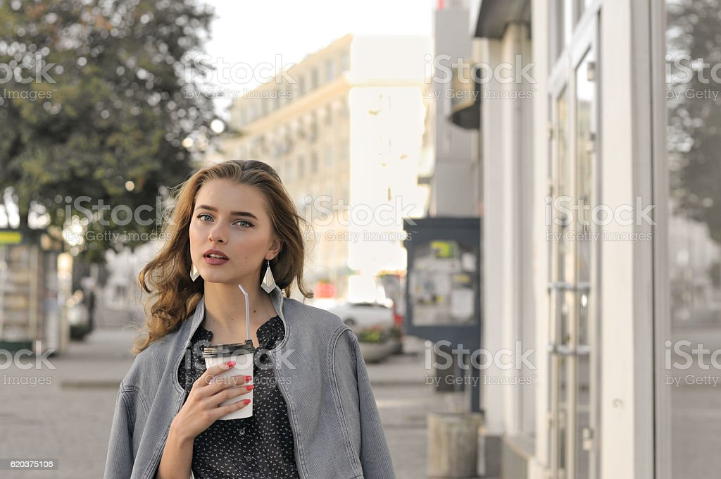 Girl goes on the sidewalk and drinking coffee foto de stock royalty-free
