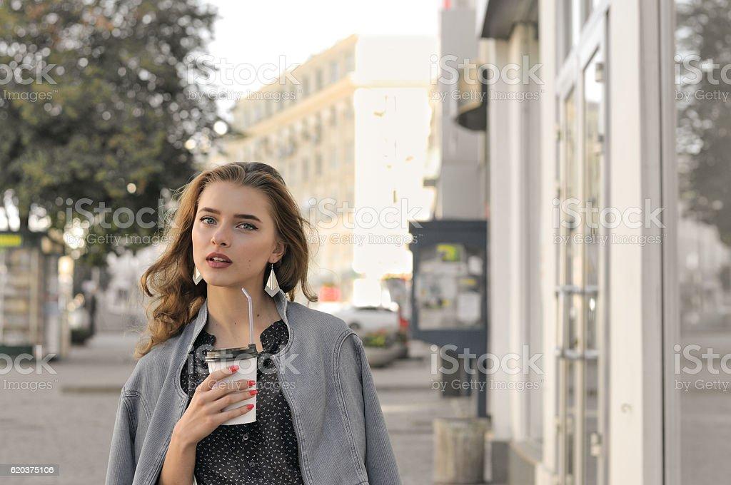 Girl goes on the sidewalk and drinking coffee zbiór zdjęć royalty-free