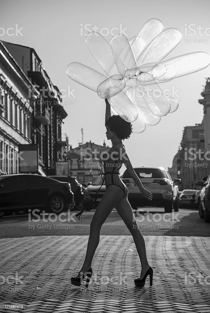 girl going down the street with balloons stock photo