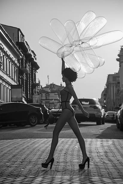 Chica va por la calle con globos - foto de stock