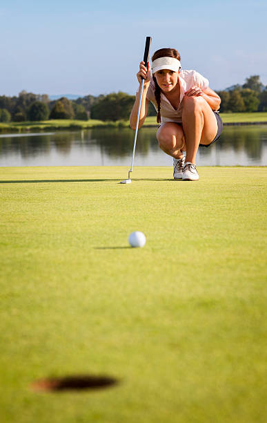 girl golfer analyzing green for putting ball into cup. - female golfer stock photos and pictures