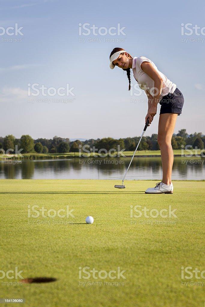 Fille de balle de golf sur le putting green. - Photo