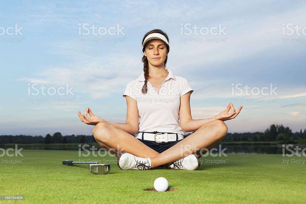 Fille assise dans la posture de yoga de golf sur le parcours de golf. - Photo