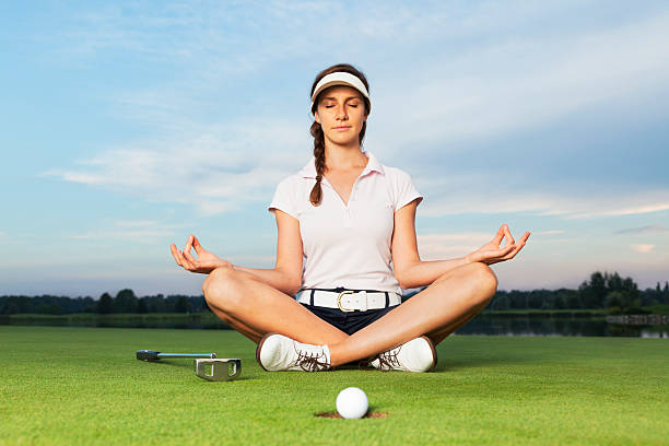 Girl golfer sitting in yoga posture on golf course. stock photo