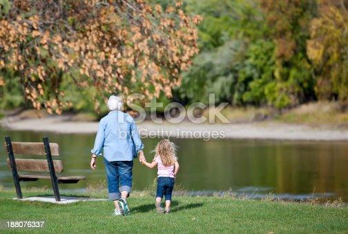 istock Girl & Grandma Walking to Riverbank Park Bench 188076337