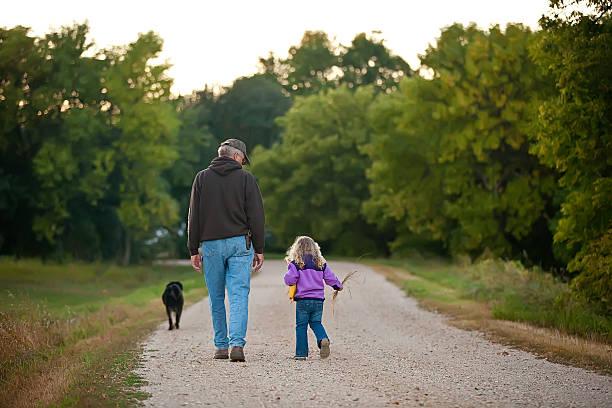 Girl & Grandpa Going for a Walk stock photo
