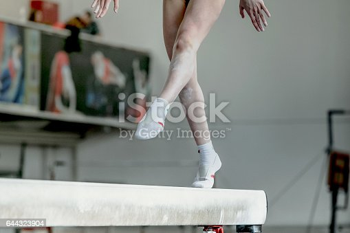 girl gymnast athlete during exercise on balance beam in gymnastics competitions