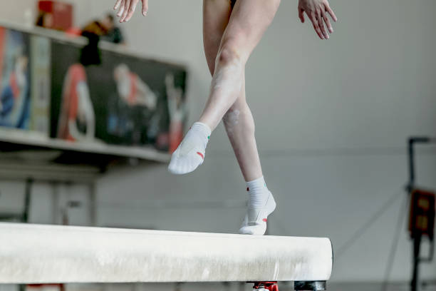 girl gymnast athlete during exercise on balance beam in gymnastics competitions - balance beam stock photos and pictures