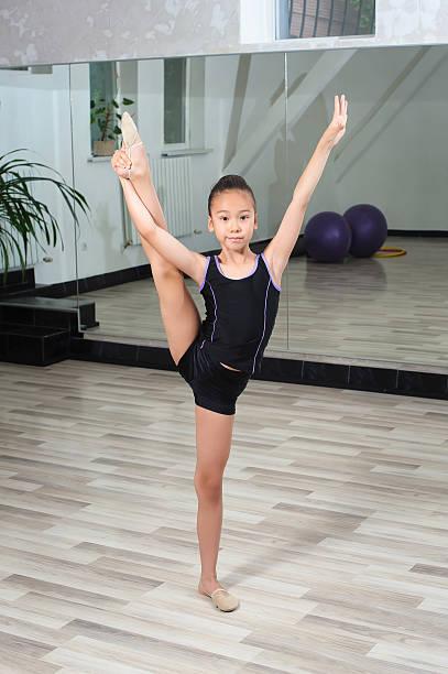 Girl gymnast doing splits in gymnasium stock photo