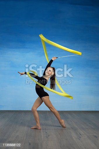 Girl gymnast in a black gymnastic swimsuit makes a spiral in the air with a yellow ribbon on a blue sky background. Vertical
