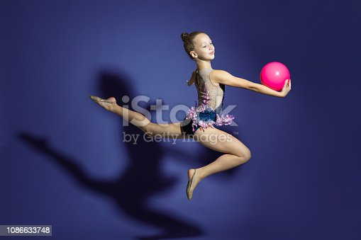 girl gymnast performs a jump with the ball. Frozen motion. Purple background Child in a bathing suit for rhythmic gymnastics.