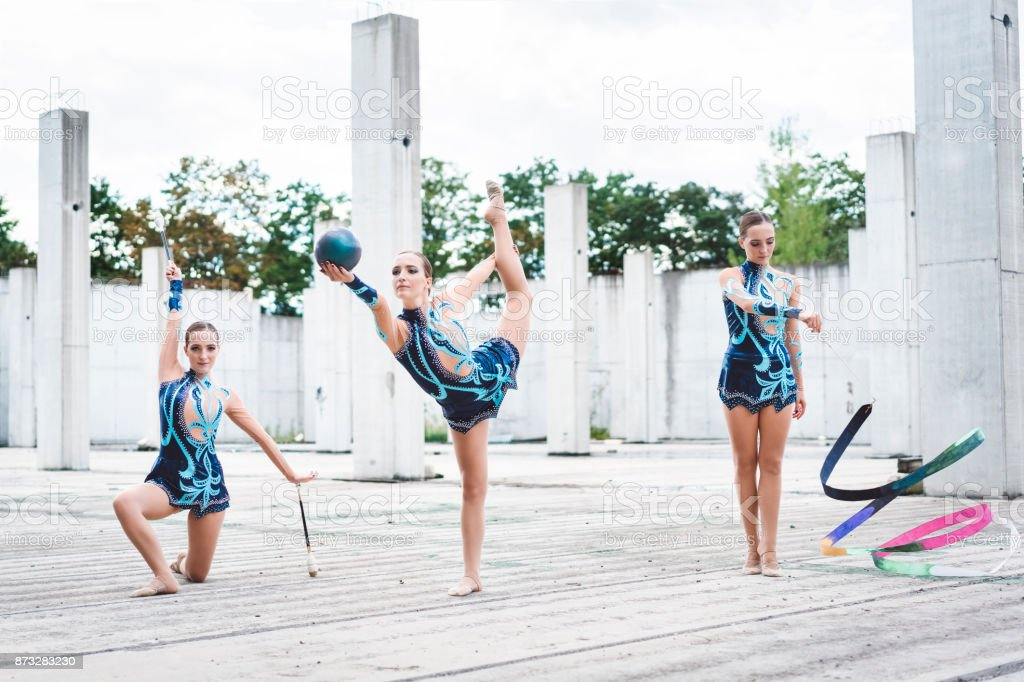 Teen girl practising rhythmic gymnastic, holding a blue ball,...